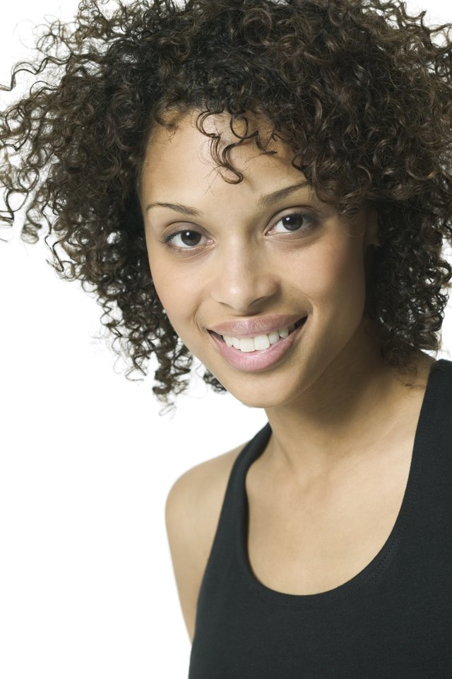 close up portrait of a young adult woman in a black tank top as she smiles