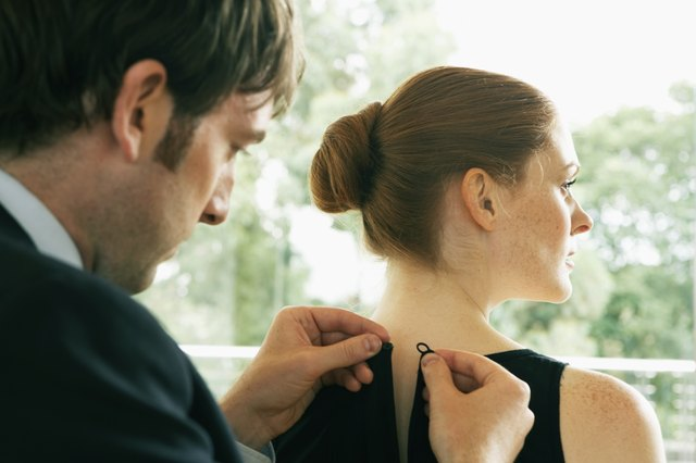 Young man buttoning young woman's dress, rear view, close-up