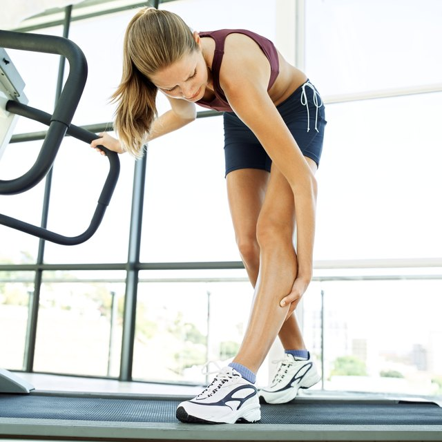 low angle view of a young woman on a treadmill holding her calf