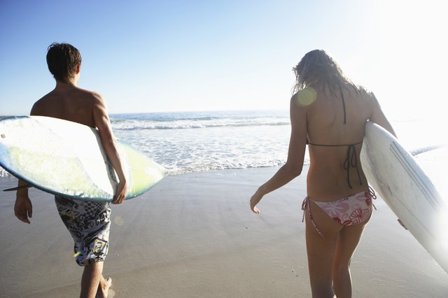 Teenage boy (14-16) and young woman carrying surfboards on beach