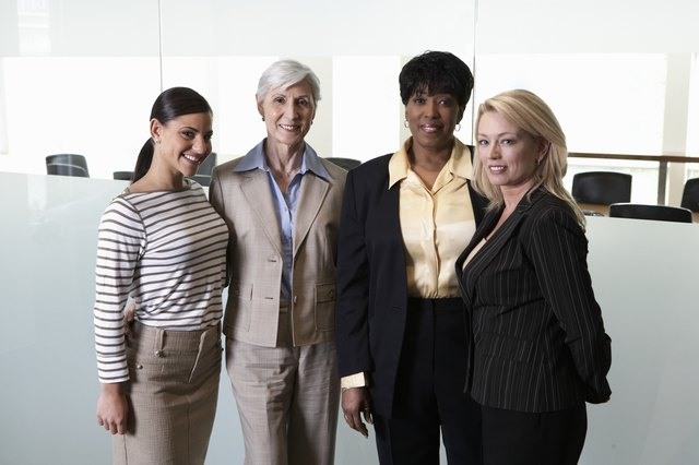 Four businesswomen standing outside boardroom, smiling, portrait