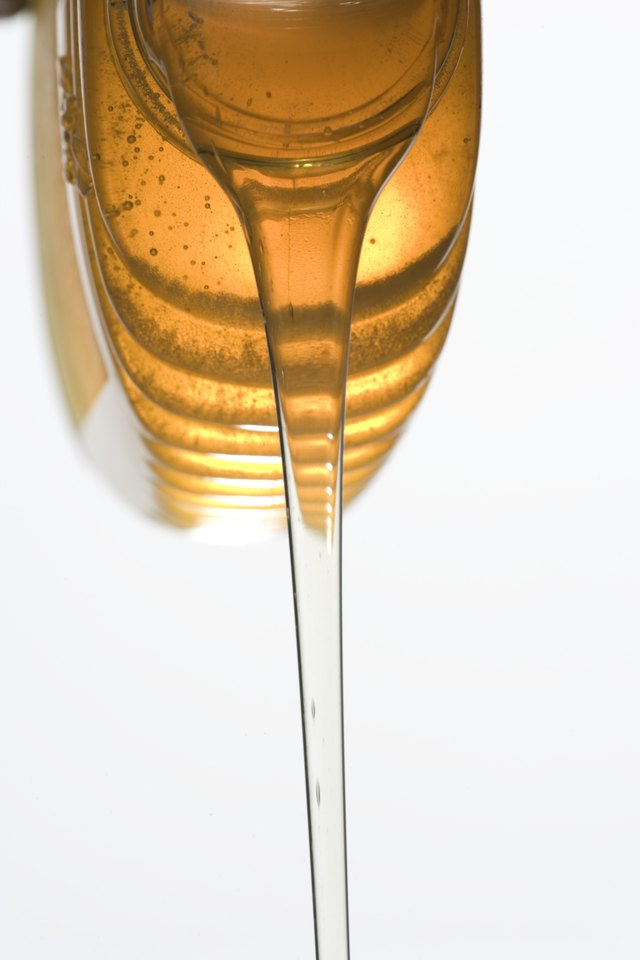 Honey pouring from jar, close-up