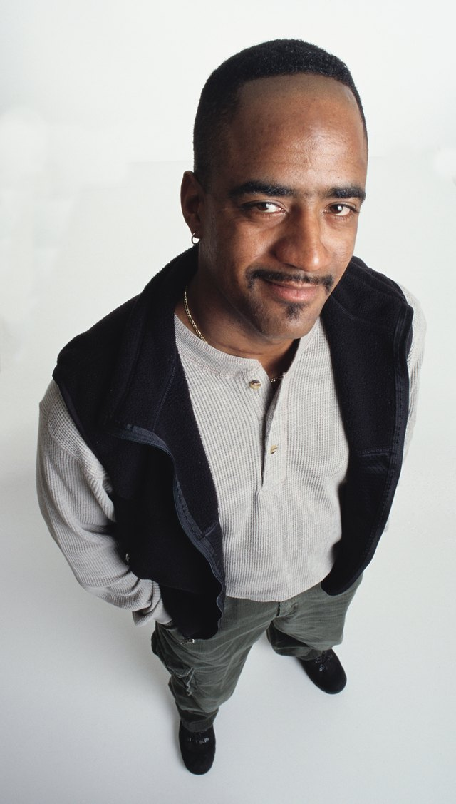 handsome young african american adult male with short hair and an earring and facial hair wearing a fleece vest and khakis stands looking up at the camera with an apprehensive expression