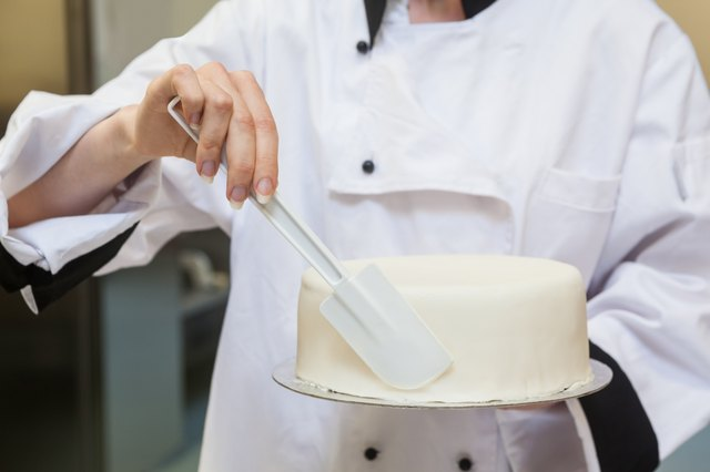 Chef finishing a cake with icing
