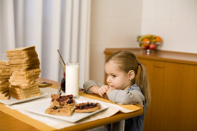 Girl looking at bread slices with peanut butter and jelly