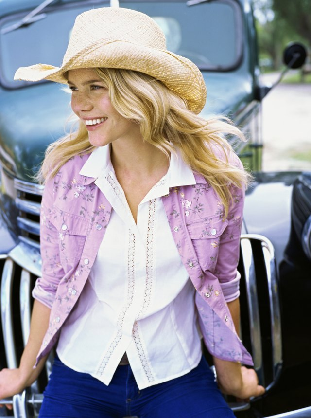 Side profile of a young woman wearing a cowboy hat, smiling