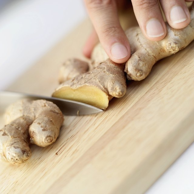 close-up of a person cutting ginger on a cutting board