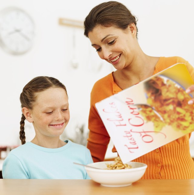 Young mother pouring cereal from a box into a young girl's (8-10) bowl