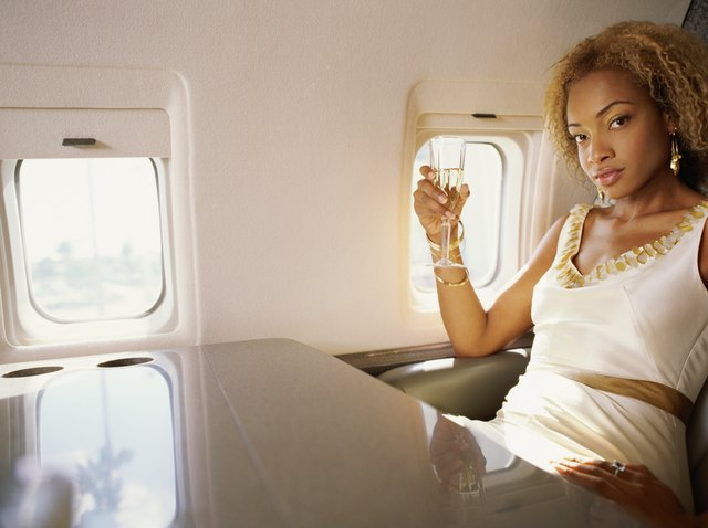 Close-up of a mid adult woman sitting in an airplane, drinking champagne