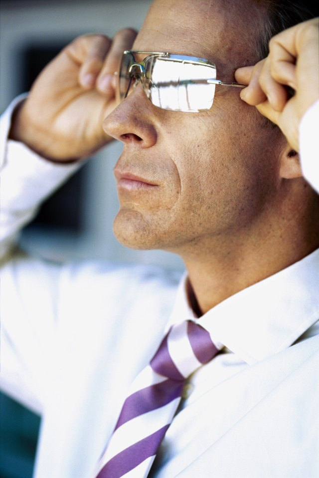 side profile of a businessman putting on sunglasses