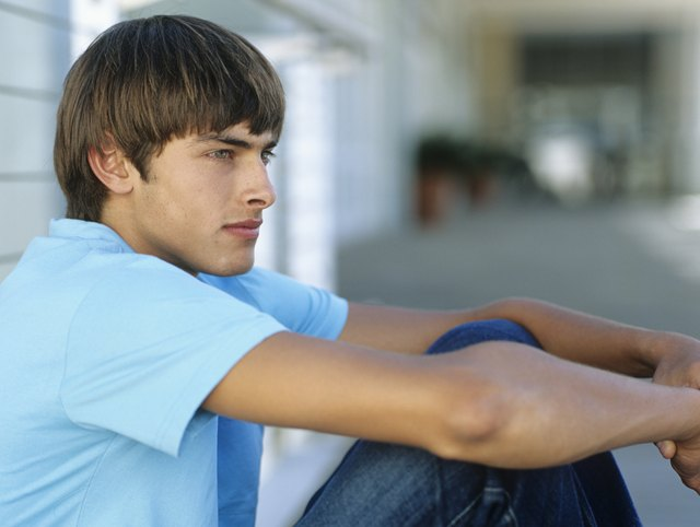 Teenage boy (16-17) sitting ob balcony,leaning on railing,side view