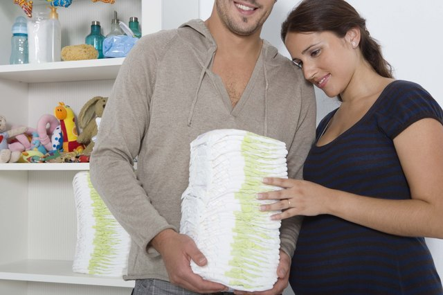 Expecting couple with diapers in nursery