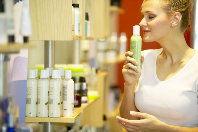 Woman smelling bottle of lotion