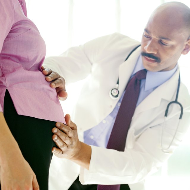 portrait of a young male doctor feeling the stomach of a pregnant woman