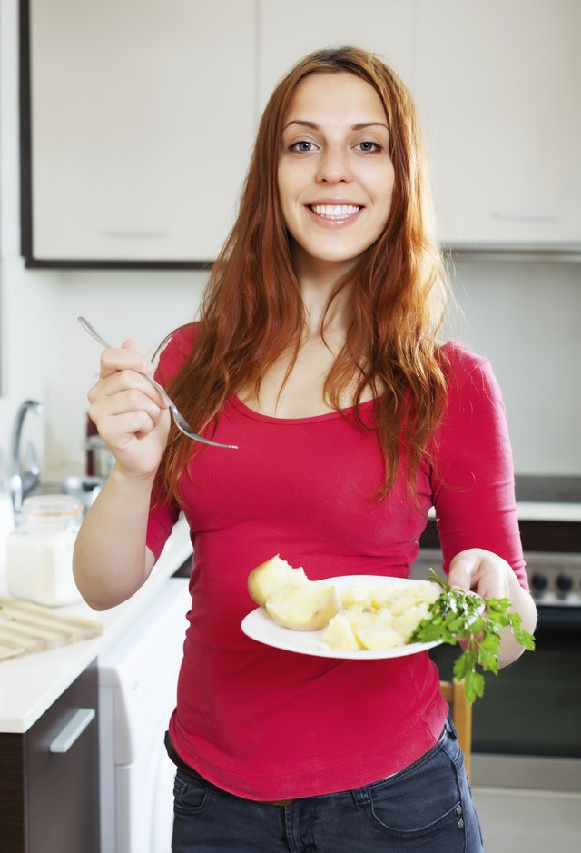 positive  ordinary woman eating potato
