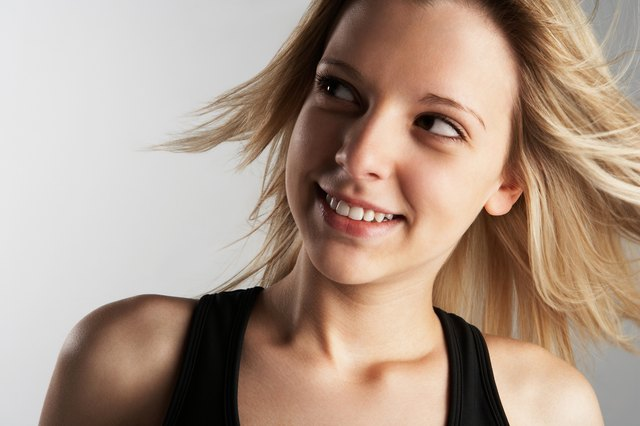Studio head shot of smiling woman with windblown hair