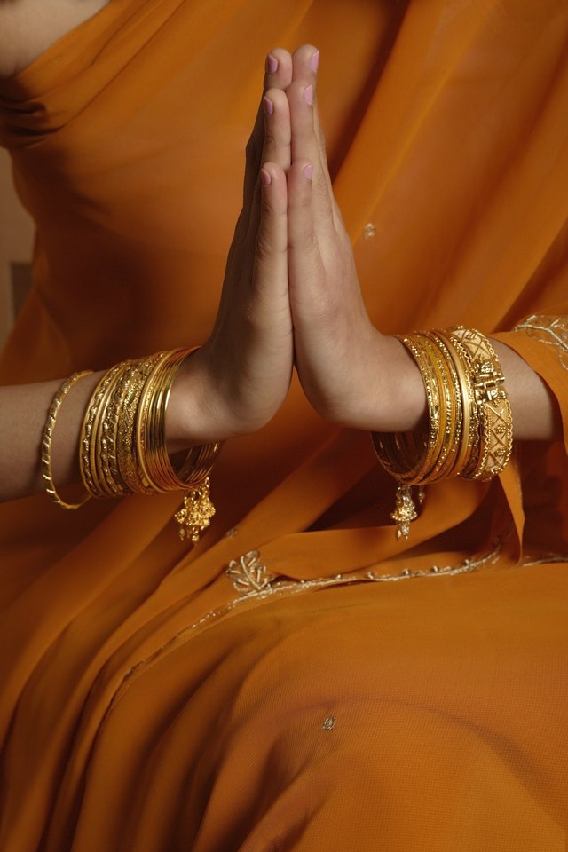 Woman wearing sari and bracelets in greeting pose