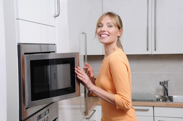 blond woman opening a microwave
