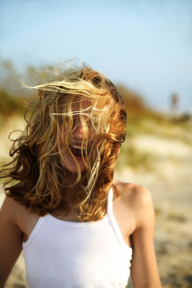 Girl on windy beach with hair covering face, Bald Head Island, North Carolina
