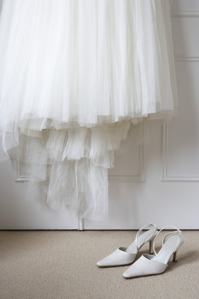 White shoes on floor beneath wedding dress hanging outside wardrobe