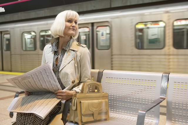 Mature woman sitting in subway platform, holding newspaper, looking away