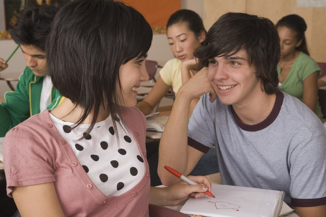 Teenage boy and teenage girl flirting in classroom
