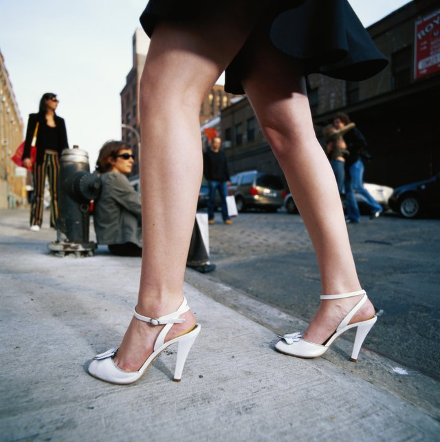 Woman in high heeled shoes walking on pavement, low section