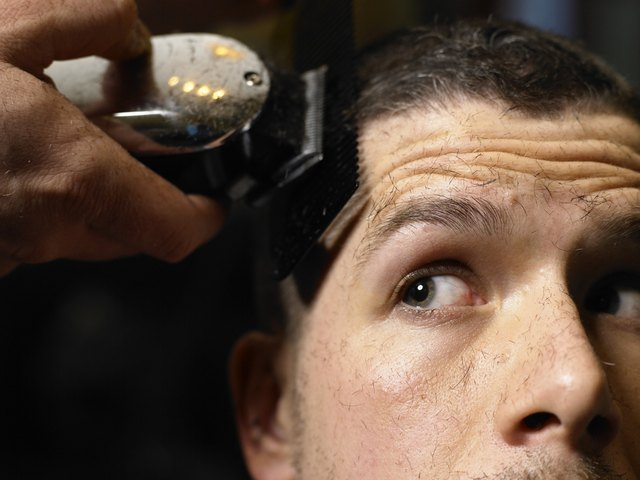 Barber shaving man's hair with electric razor, close-up
