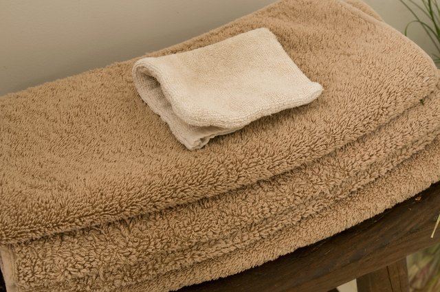 Towels and washcloth stacked on bathroom stool