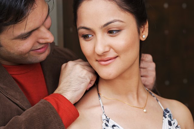 A man adorning a woman with jewelry