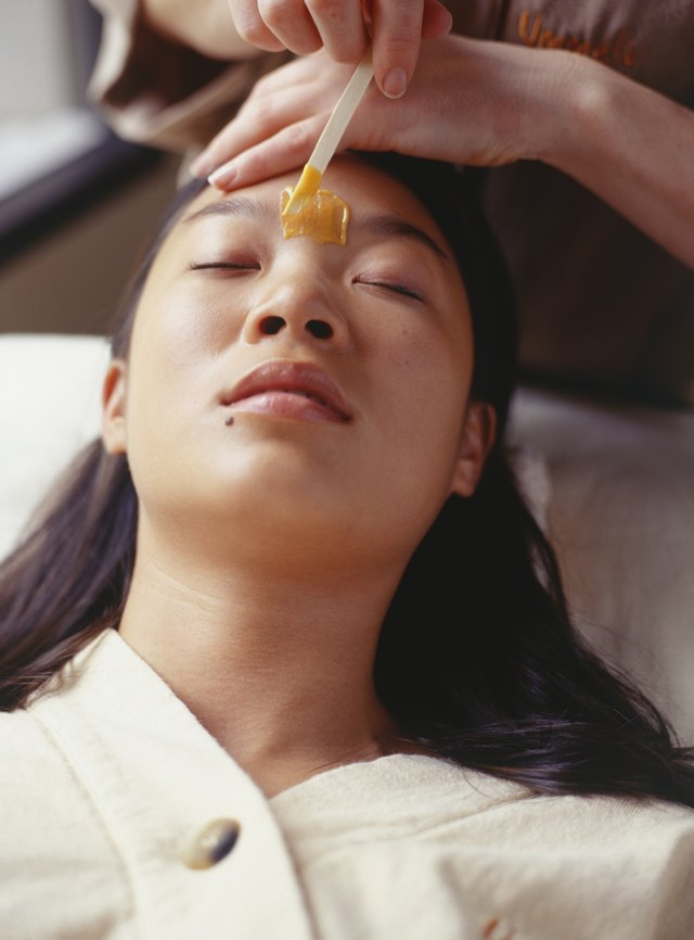 Young woman having eyebrows waxed in beauty parlour, elevated view, close-up