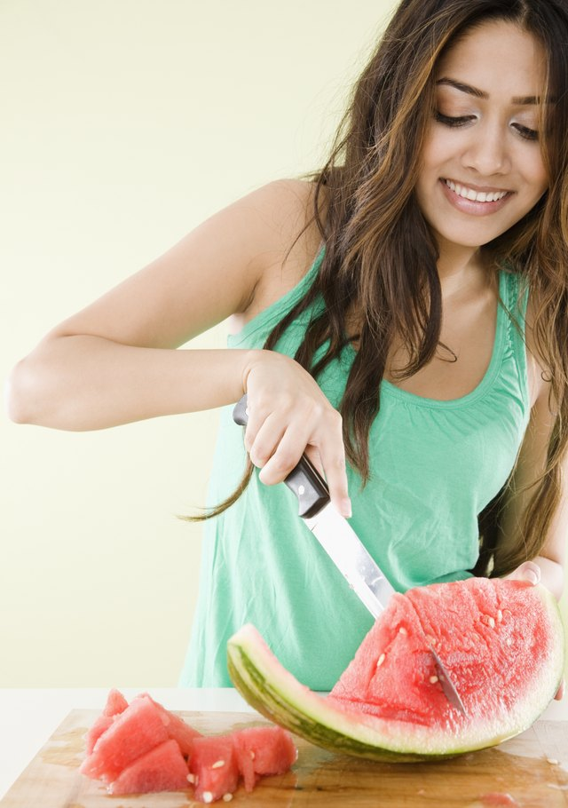 Middle Eastern woman cutting watermelon