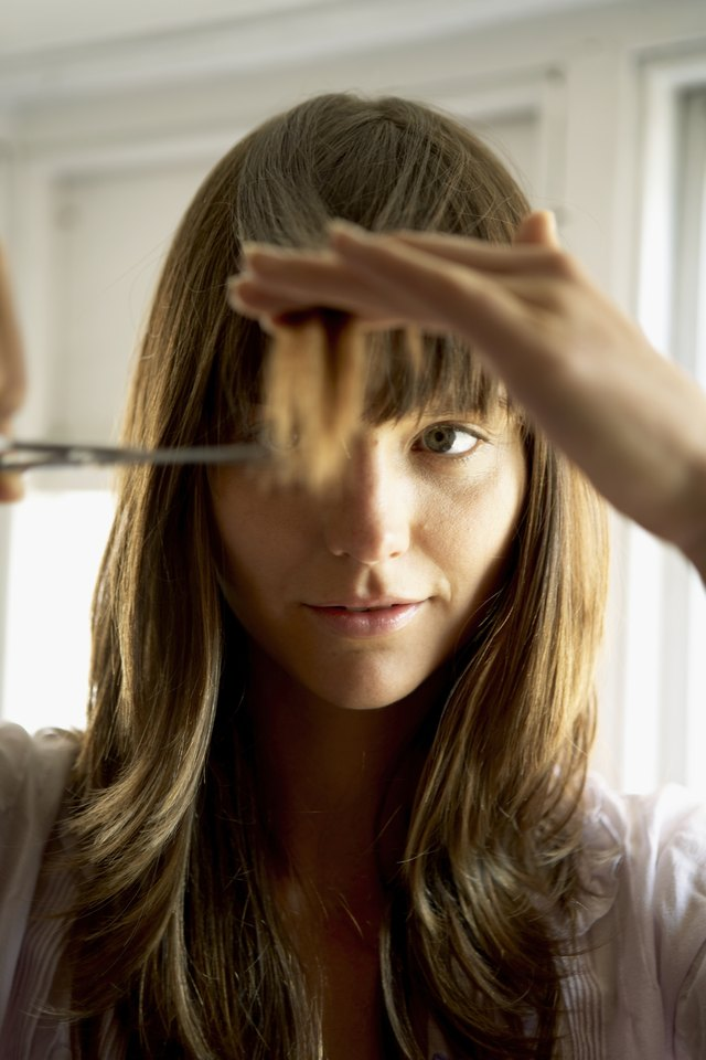 Woman cutting hair with scissors, close-up