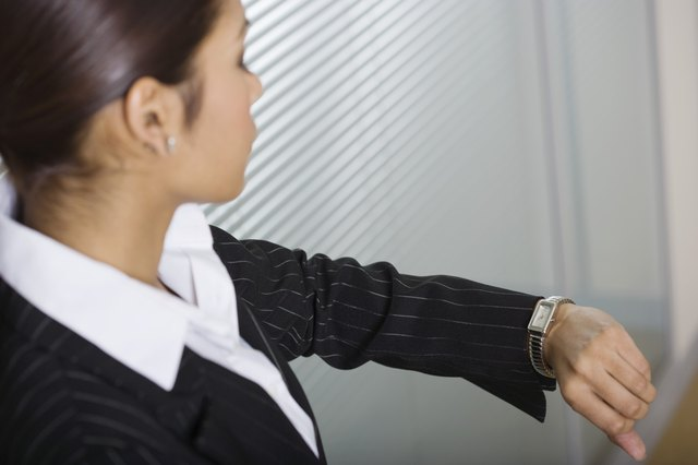 Businesswoman checking wristwatch