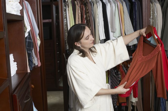 Mature woman looking at a dress in a walk-in wardrobe