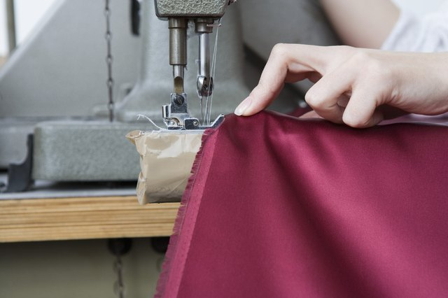 Hand using sewing machine on fabric