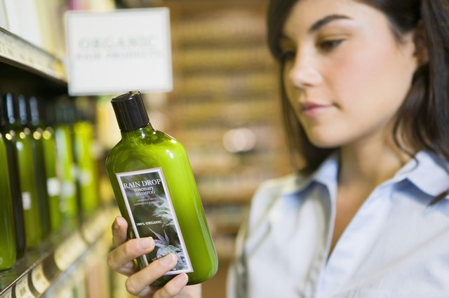 Woman reading label of organic shampoo