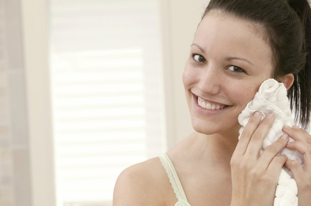 Woman drying face with towel