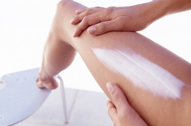 Woman applying lotion to leg