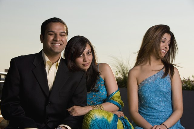 Young man sitting with two young women