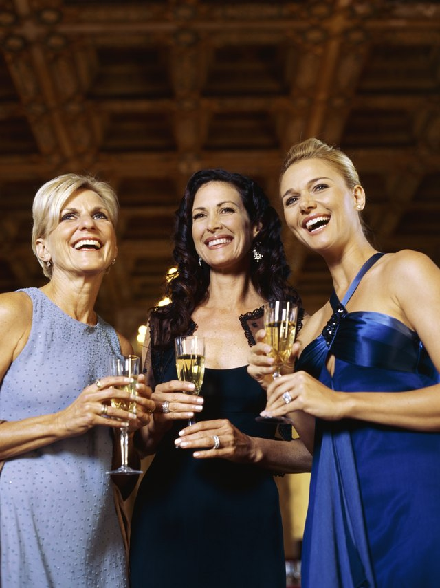 Low angle view of three women holding champagne flutes
