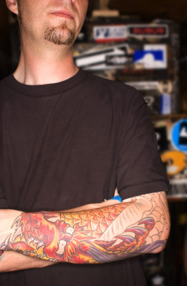 Man with dragon tattoo on forearm