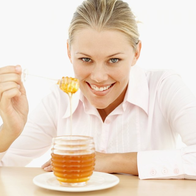 close-up of a young woman holding a honey dipper over a jar of honey