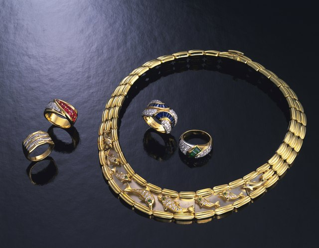 Gold rings and necklace with jewels, high angle view, black background