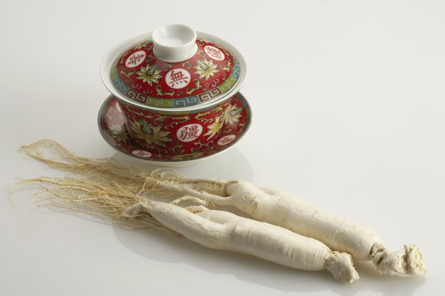 Two ginseng roots next to tea cup