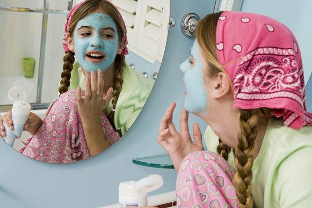 Preteen girl applying facial mask