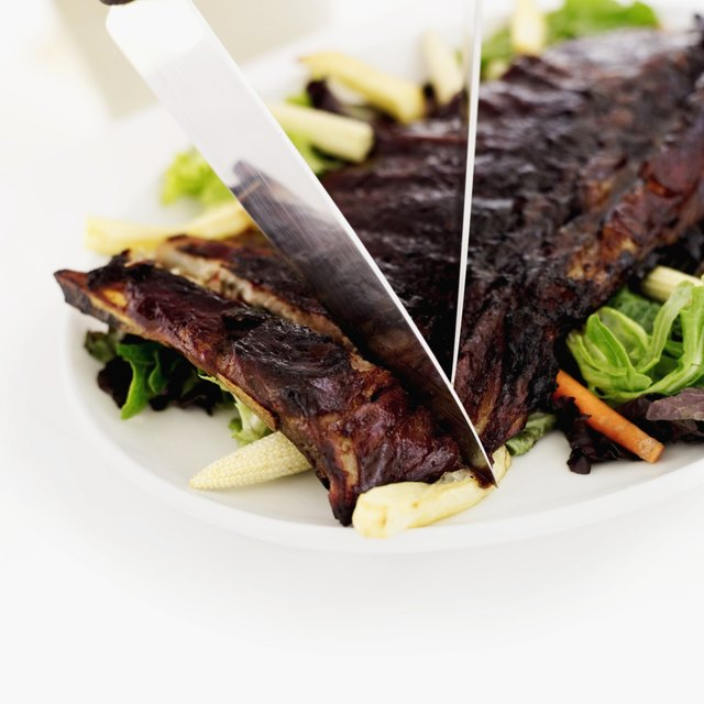 Close-up of two knives cutting into spareribs