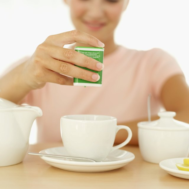 Close-up of a woman's hand dispensing sweetener into a cup of tea