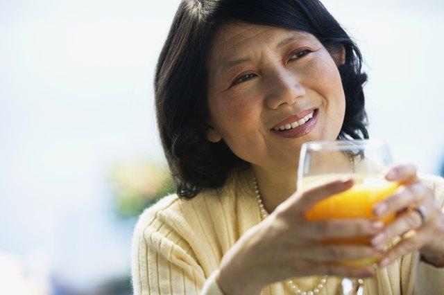 Asian woman drinking orange juice