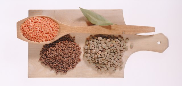 Bay leaf, chickpea, green pea, lentil and spoon on chopping board, close-up